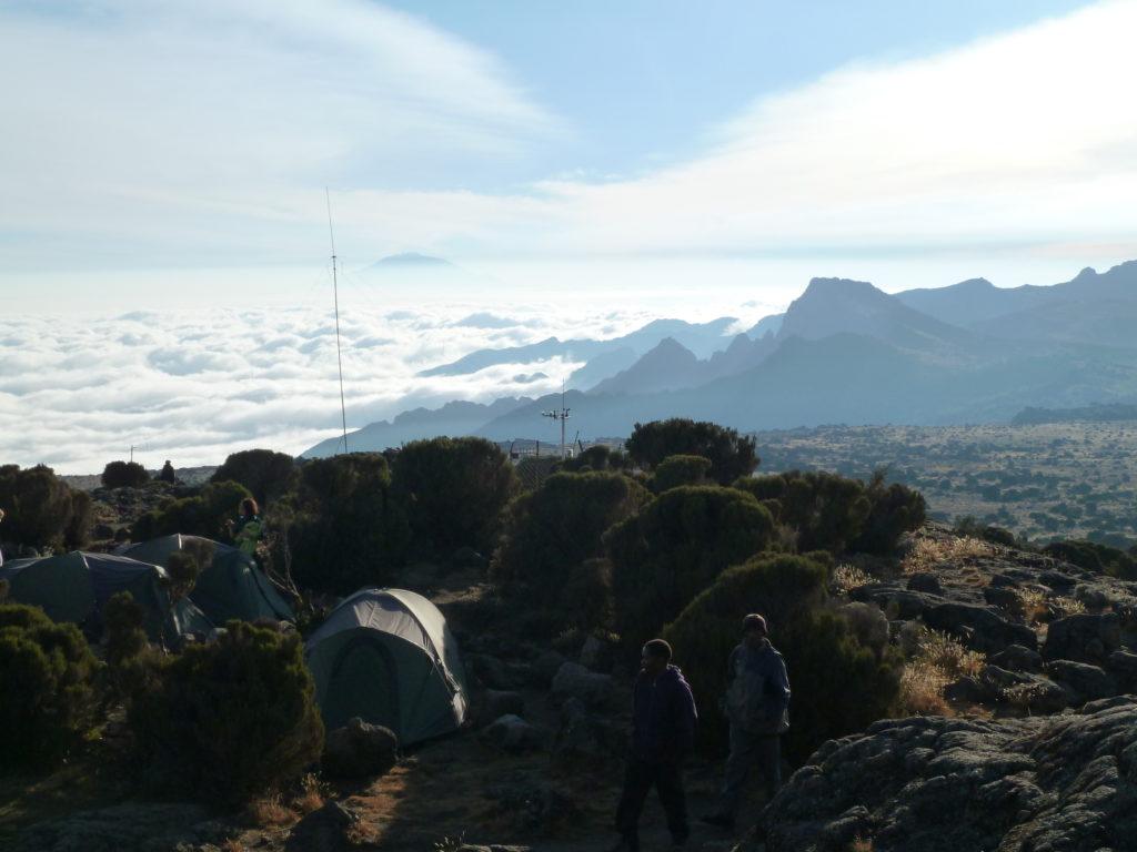 Climbing Mt Kilimanjaro View of Mt Meru peeking through clouds. Taken from Shira Hut Camp Site