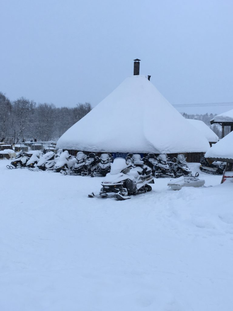 """Snow hotel Snowmobiles lightly"""" dusted with snow."""