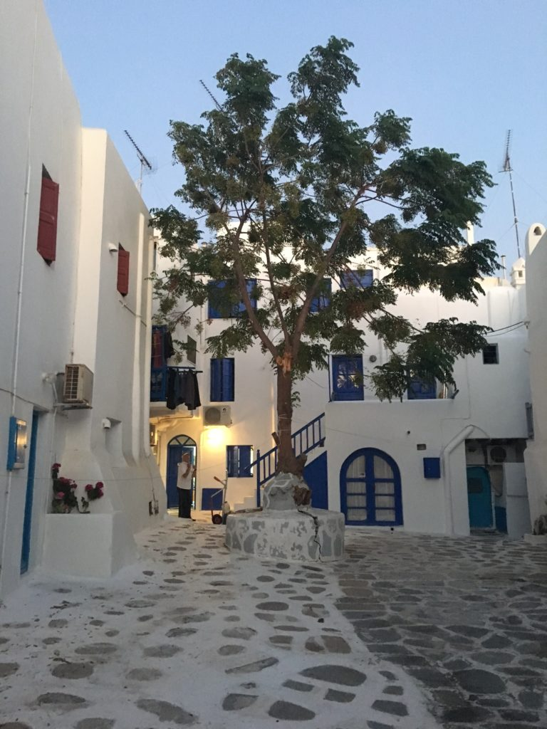 Mykonos white-washed houses as evening arrives. Showing the contrasting blue door and window frames and cobbled courtyards. www.gypsyat60.com