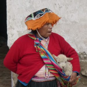 Woman from Peru carrying baby lamb in a sling. www.gypsyat60.com