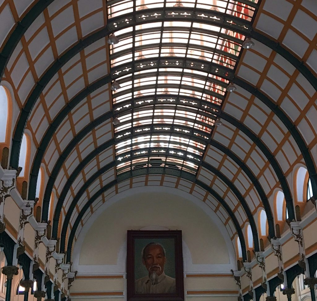 Impressive Ceiling of the Saigon Post Office with Ho Chi Minh featured on the end wall. www.gypsyat60.com