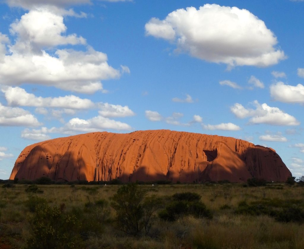 Uluru (Ayers Rock), Northern Territory, Australia. Amazing contrast between blue sky, clouds, red rock and green surrounding bush (scrub). www.gypsyat60.com